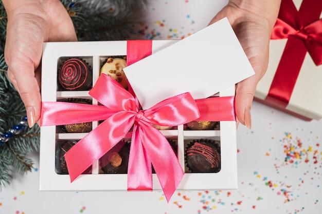 Doces de trufas de chocolate artesanais em uma mulher com as mãos em um fundo de natal com cartão de visita