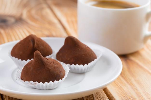 Doces de trufas de chocolate em prato na mesa de madeira