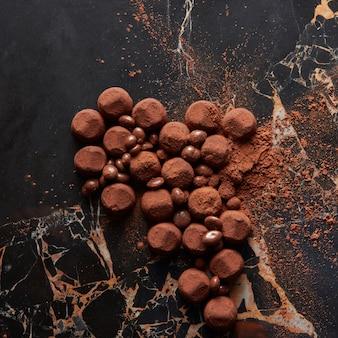 Doces de trufas em uma superfície de mármore escuro.