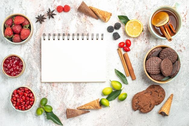 Doces de vista de cima, caderno branco, uma xícara de chá, biscoitos, geléia, paus de canela, romã, frutas, limão
