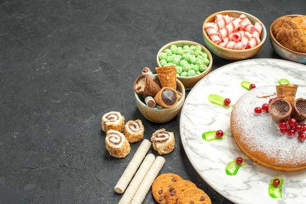 Doces de vista lateral um bolo apetitoso com frutas waffles biscoitos doces coloridos