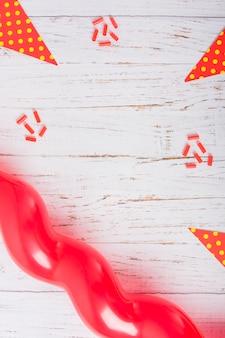 Doces decorados, papel de bolinhas e balão na mesa de madeira