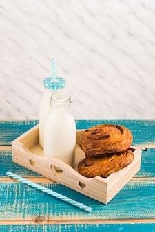 Doces dinamarqueses com garrafa de leite na bandeja de madeira perto de palha sobre a mesa de madeira azul