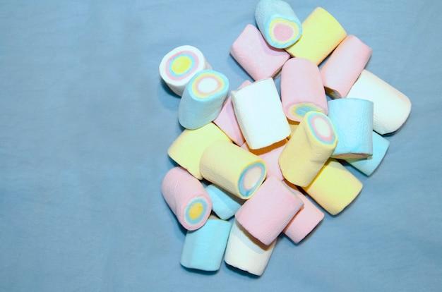 Doces do marshmallow das cores pastel na pilha no fundo azul vista superior com espaço da cópia