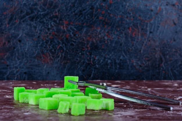 Doces doces em forma de travesseiro verde em uma superfície clara
