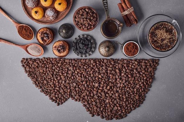 Doces e café na superfície cinza.