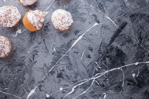 Doces e cremosos mini cupcakes espalhados pelo mármore.