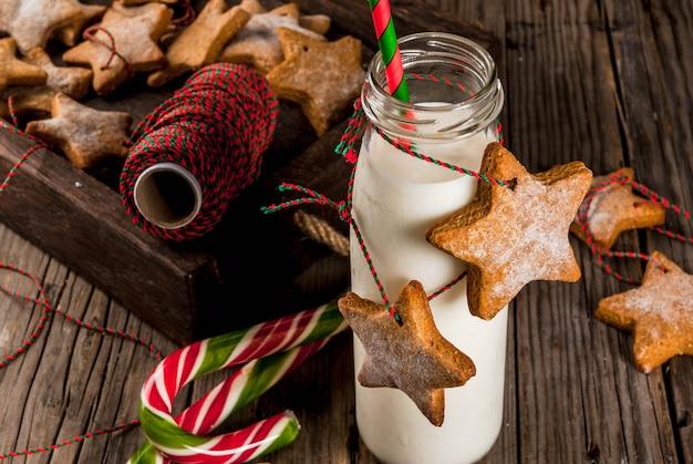 Doces e guloseimas de natal, garrafas com leite para o papai noel com biscoitos estrela de gengibre com corda de decoração, de madeira velha,