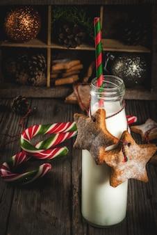 Doces e guloseimas de natal, garrafas com leite para o papai noel com biscoitos estrela de gengibre com corda de decoração e decorações de natal, de madeira velha,