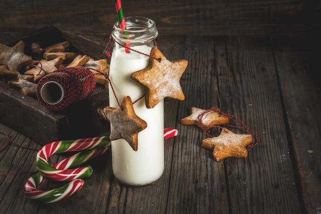 Doces e guloseimas, garrafas de leite para o papai noel com biscoitos estrela de gengibre com corda de decoração, de madeira velha,