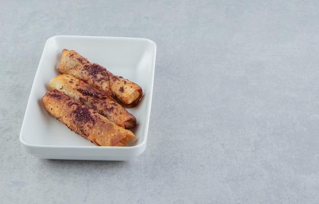 Doces em forma de charuto frito em uma tigela branca.