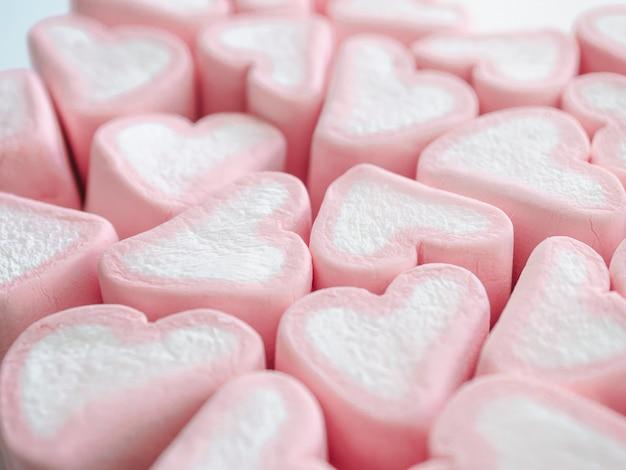 Doces em forma de corações de marshmallow rosa branco.