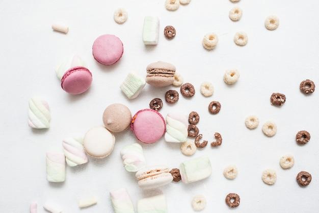 Doces em fundo branco. macaroons coloridos, zéfiros e variedade de cereais matinais