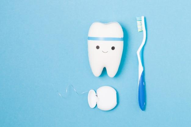 Doces, escova de dentes, fio dental e dente de brinquedo em uma superfície azul