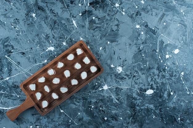 Doces fatiados em uma placa, na mesa azul.