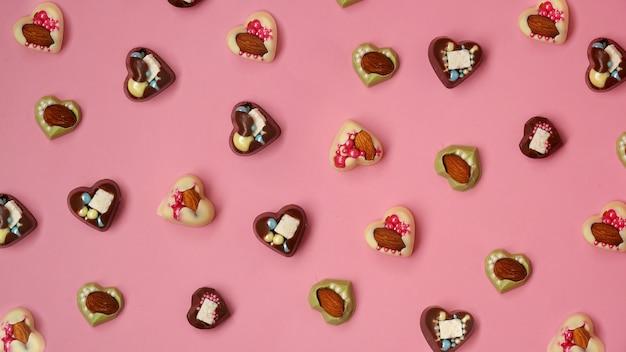Doces feitos à mão em forma de coração em um fundo rosa