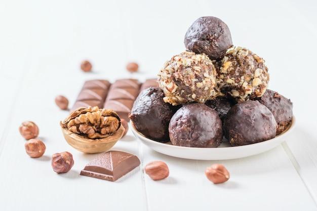 Doces feitos em casa de nozes, frutas secas e chocolate em uma mesa de madeira branca.