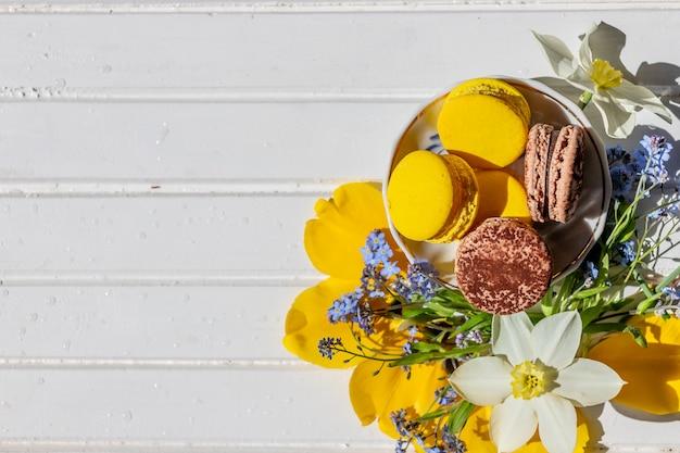 Doces franceses do bolinho de amêndoa e flores macias das flores no fundo de madeira.