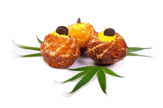 Doces frescos assados com maconha, três cupcakes com folhas de planta cannabis isoladas no fundo branco, doces, sobremesa.