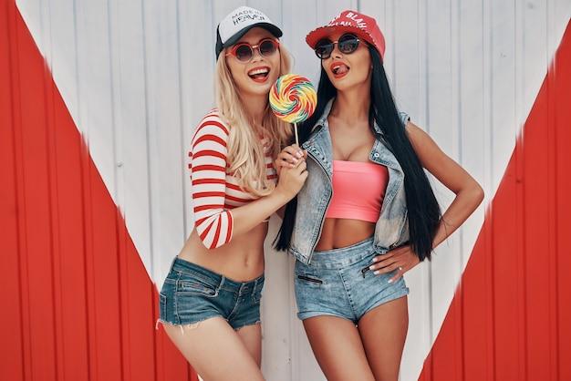 Doces garotas. duas jovens brincalhonas segurando um pirulito grande e olhando para a câmera em pé contra um fundo colorido
