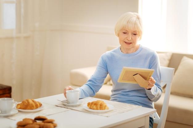 Doces lembranças. mulher alegre abaixando a cabeça e olhando para a foto enquanto toma o café da manhã