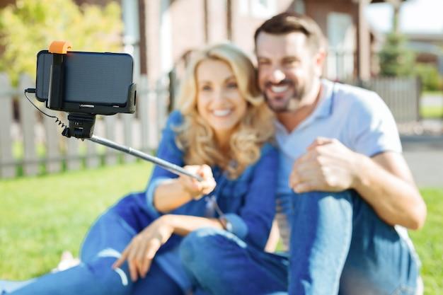 Doces lembranças. o foco está em um bastão de selfie com um telefone preso por uma mulher encantadora sentada ao lado de seu amado marido e tirando uma selfie