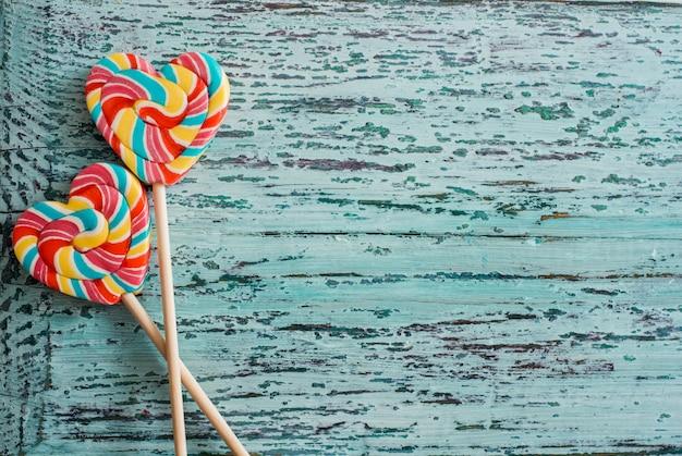 Doces listrados coloridos do arco-íris dos pirulitos como o coração no fundo azul. conceito engraçado.