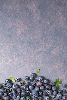 Doces mirtilos frescos em fundo escuro de concreto. vista superior e cópia da imagem do espaço
