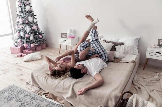 Doces momentos. jovem bonito barbudo e a esposa usando meias brancas grossas curtindo a manhã