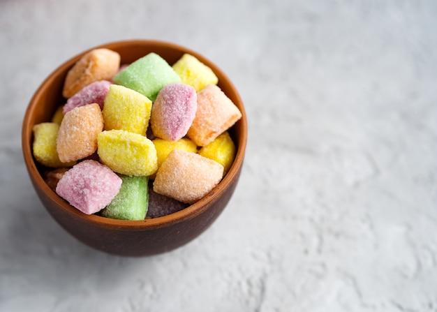 Doces multicoloridos (almofadas de doces) em um copo de barro