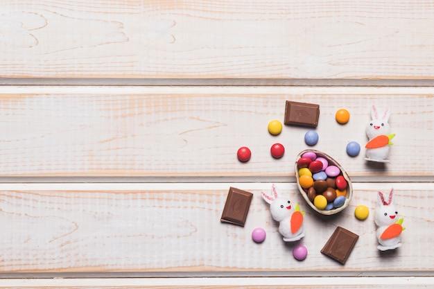 Doces multicoloridos em casca de ovo; gemas; coelhos e pedaços de chocolate na superfície de madeira