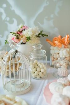 Doces, nozes em açúcar, marshmallows, merengue - barra de chocolate no casamento. decoração, mesa doce