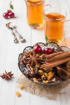 Doces orientais, tâmaras e passas de frutas secas, canela e anis estrelado num prato