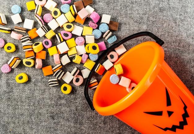 Doces ou travessuras balde de abóbora de lado para coletar doces no halloween