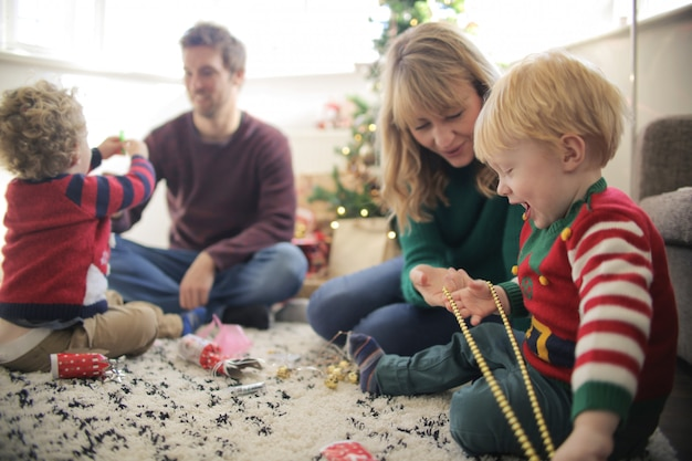 Doces pais brincando com seus filhos com decorações de natal