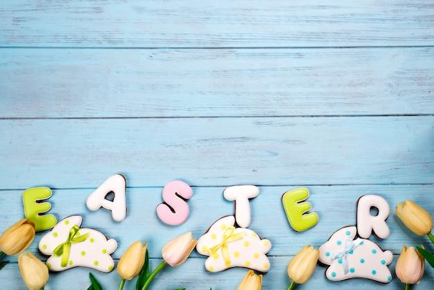 Doces para celebrar a páscoa. pão de mel em forma de coelhinho da páscoa e carta de páscoa, tulipas
