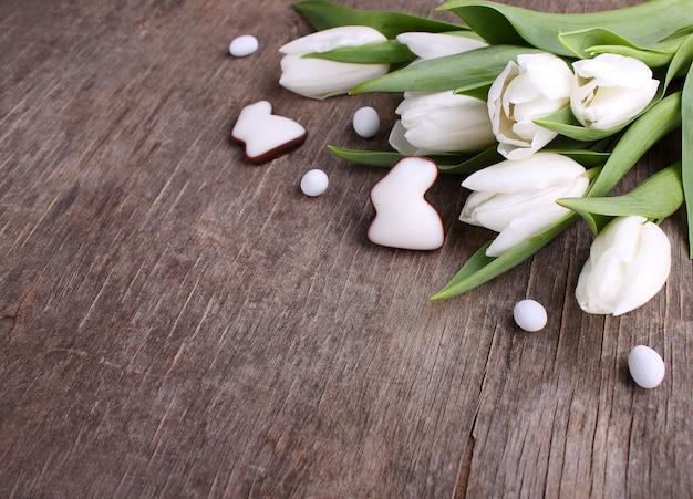 Doces para celebrar a páscoa. tulipas brancas, ovos de chocolate e coelho. fundo de madeira velho.