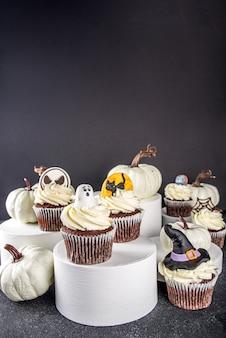 Doces para festa de halloween. cupcakes de halloween caseiros engraçados em carrinhos modernos e pódios em fundo escuro. conceito de guloseimas para festa de halloween