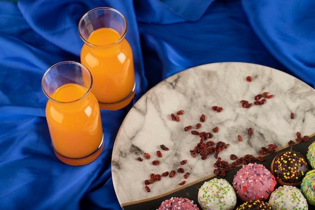 Doces pequenos donuts coloridos com garrafas de suco de laranja.