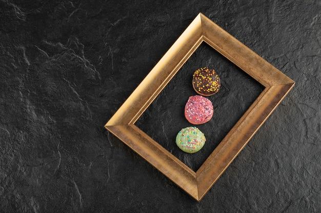 Doces pequenos donuts com granulado em uma mesa preta.