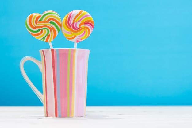 Doces redondos coloridos e doces de coração em uma cor pastel de taças listras verticais na mesa de madeira