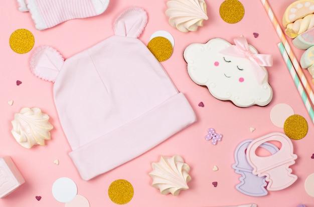 Doces, roupas de bebê e acessórios no fundo rosa