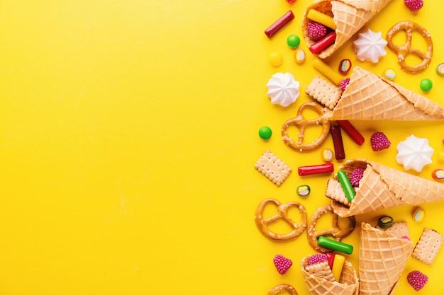 Doces saborosos engraçados no fundo amarelo