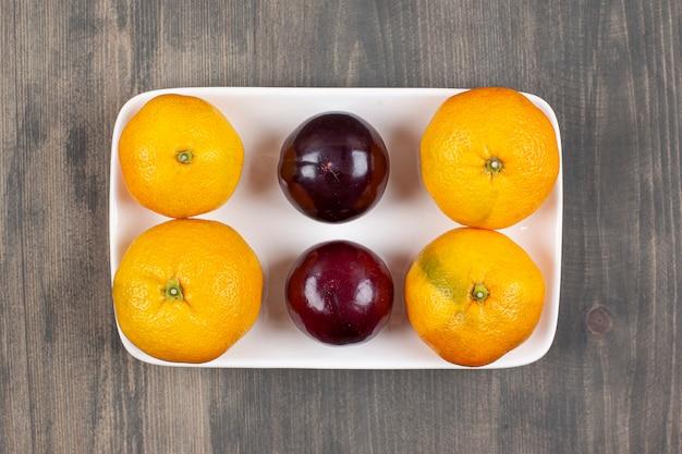 Doces tangerinas com ameixas em uma mesa de madeira. foto de alta qualidade