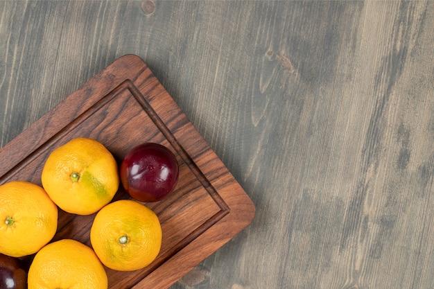 Doces tangerinas com ameixas em uma tábua de madeira. foto de alta qualidade