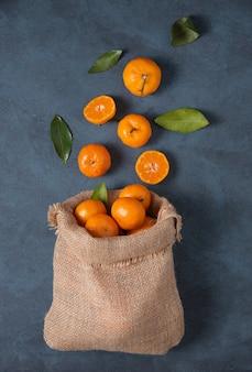 Doces tangerinas com folhas verdes caem de uma sacola de artesanato sobre um fundo azul escuro. foto escura. vista do topo
