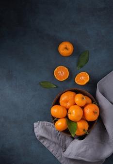 Doces tangerinas com folhas verdes em uma tigela de madeira sobre um fundo azul escuro com guardanapo cinza. foto escura. vista superior e espaço de cópia