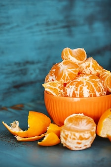 Doces tangerinas e laranjas na mesa com fundo de madeira Foto Premium