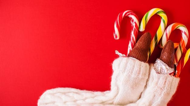Doces tradicionais de natal em fundo vermelho. bastões de doces com papai noel de chocolate calçam meias de malha. bandeira