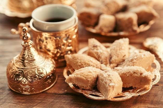 Doces turcos com café em uma mesa de madeira